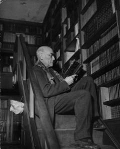 circa 1940: Andre Paul Guillaume Gide (1869 - 1951), the French novelist and philosopher, reading a book perched on the stairs of his library. He was awarded the Nobel prize for literature in 1947. (Photo by Hulton Archive/Getty Images)